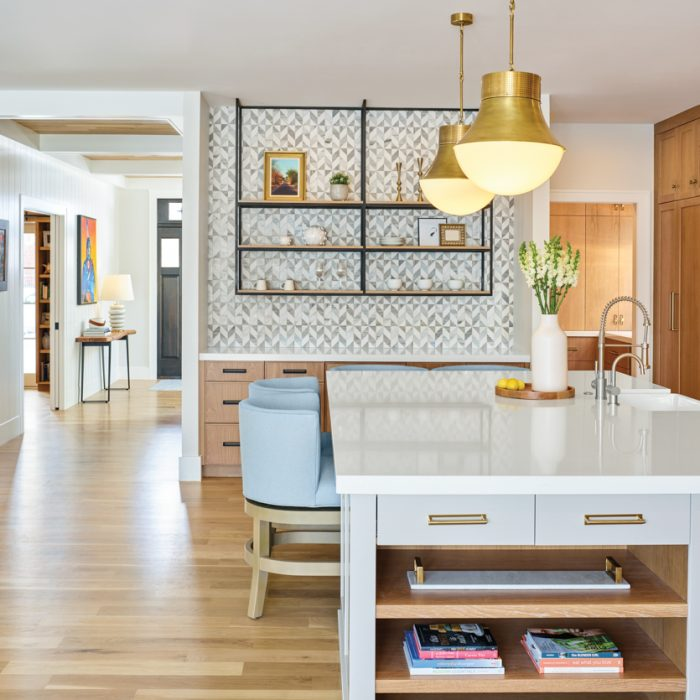 In the kitchen, a playfully patterned mosaic makes up the bar backsplash. Ballard Designs' Shelton counter stools pull up to an island--painted in Benjamin Moore's Collingwood--which was crafted by Aspen Leaf Kitchens Ltd. Antique burnished brass pendants by Visual Comfort hang above.