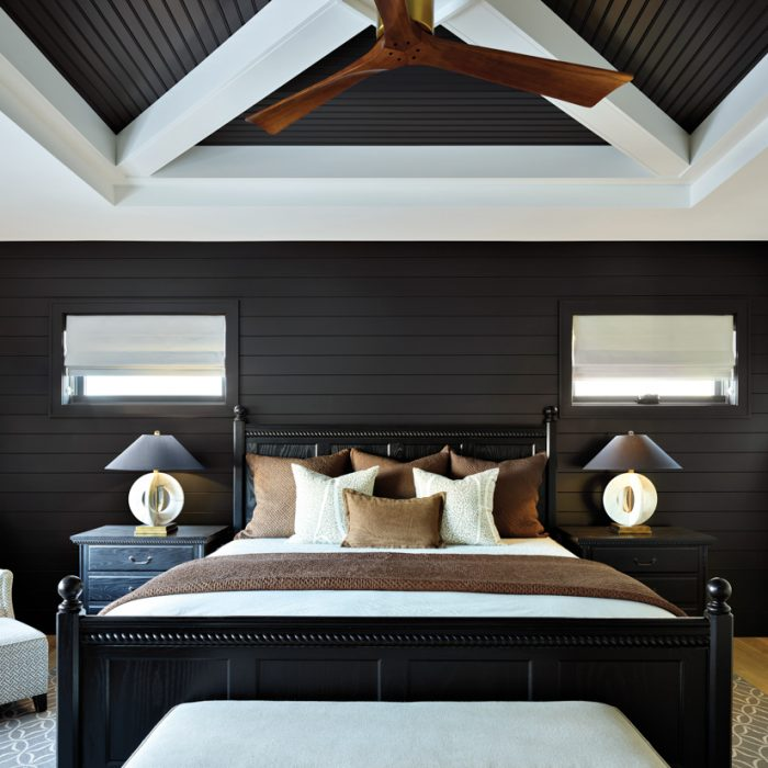 The designers transformed the master bedroom into a cozy sanctuary using the homeowners' furniture. The ceiling was paneled to add interest and texture. The ceiling and one of the walls were painted in Farrow & Ball's dark-hued Railings color, and the trim was covered with Simply White by Benjamin Moore for contrast. The Felice table lamps are by Currey & Company.