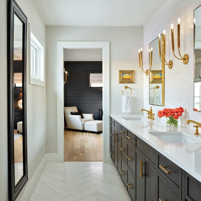 A light-colored marble vanity contrasts with dark cabinets in the master bathroom for a striking effect. The cabinetry, with brass pulls by Emtek, is by Aspen Leaf Kitchens Ltd. Brass-framed vanity mirrors by Mirror Image Home are flanked by sconces from RH. Walls are painted in Benjamin Moore's Classic Gray, and the Dolomite Corina floor tile is by Ann Sacks.