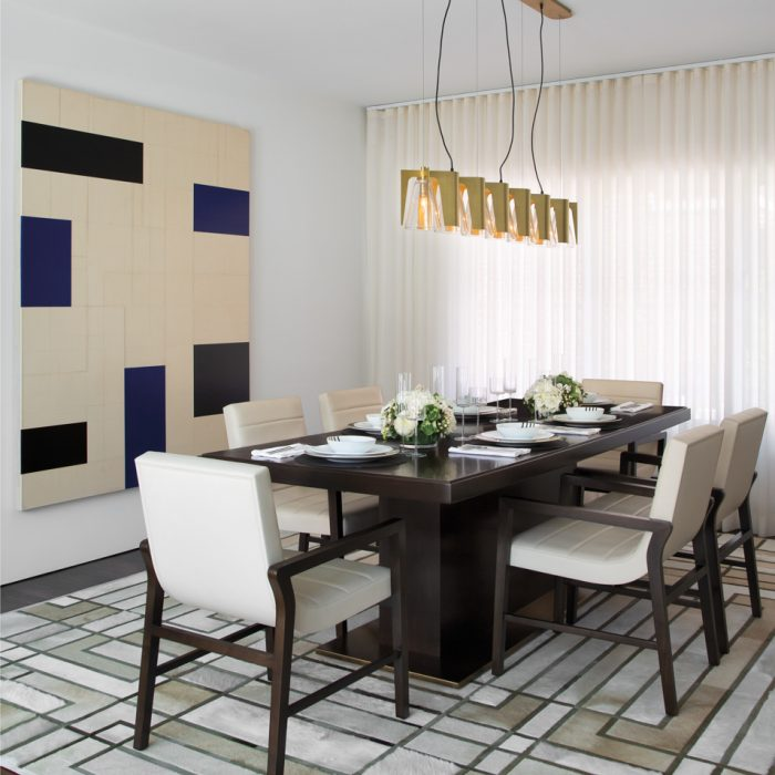 In the dining room, Dantes took cues from the neighboring living room's coffered ceiling when adding geometric elements like the hair-on-hide rug and Robert Kelly artwork. A Fuse Lighting chandelier from MOD Design lights the Anees Furniture & Design chairs and a Chai Ming Studios table.