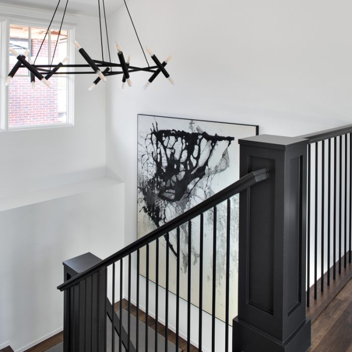 """Once we added steel posts to the staircase, the choice of light fixture was obvious,"" says Dantes, who chose a Jonathan Browning Studios chandelier fashioned from powder-coated brass tubes. In the stairwell, a Zachariah Rieke painting from William Havu Gallery is a perfect complement."