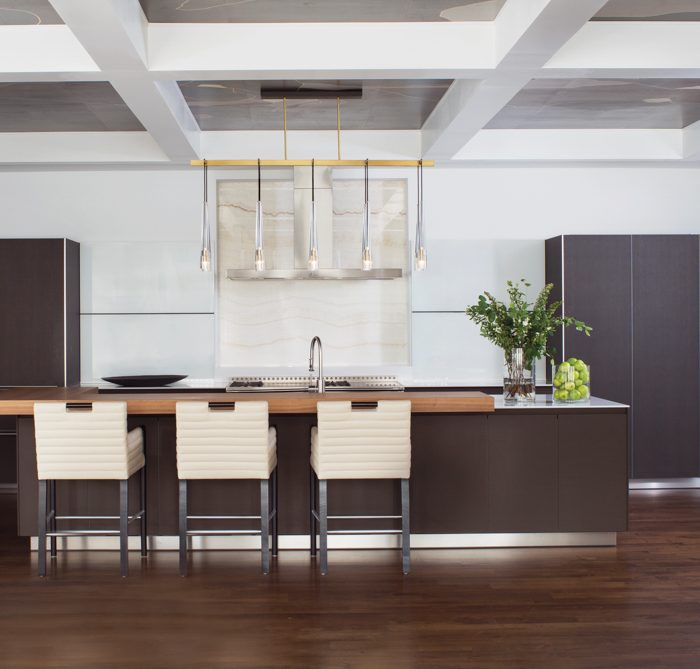 Bulthaup cabinets with a mix of matte lacquer and dark oak as well as a hand-blown crystal and bronze Jonathan Browning Studios light fixture make the kitchen stand out. A walnut slab inserted in the white quartz topped island provides the dining surface and dictated the location of the Bright Chair Company counter stools.