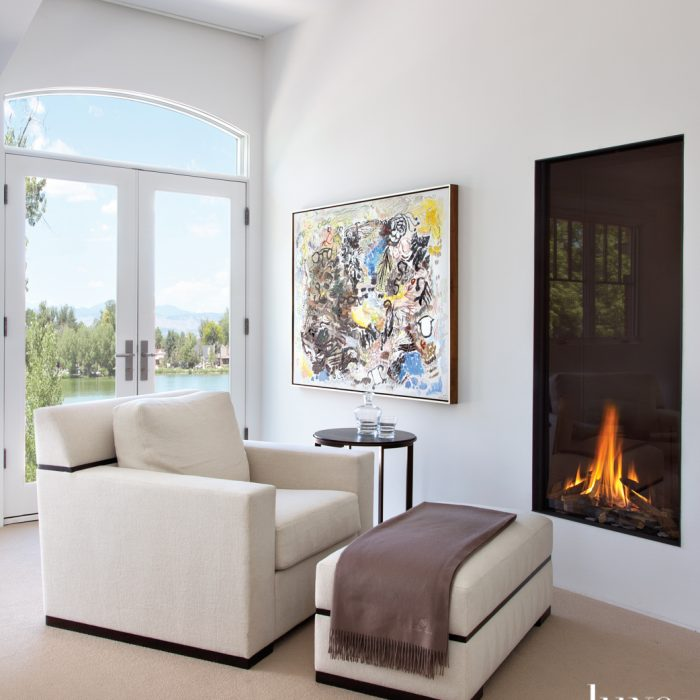 On the home's second story, designer Mikhail Dantes created a relaxing spot in the master bedroom to take in views of the lake. A Troscan chair sits beneath a Sam Scott painting purchased at William Havu Gallery. The modern fireplace is from Distinctive Mantels Designs.