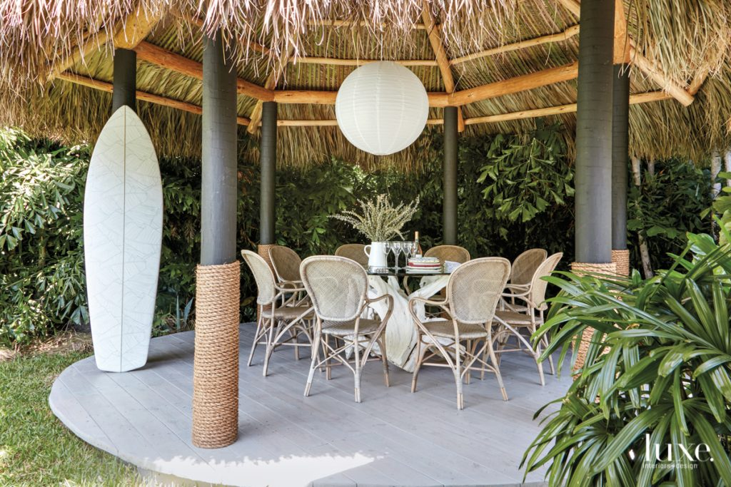 outdoor dining table with globe pendant under tiki