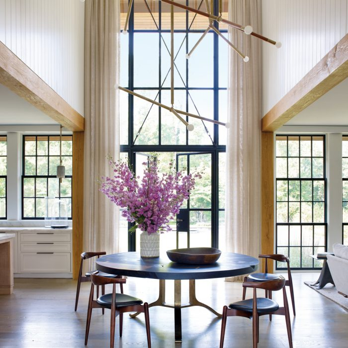 A custom chandelier from Apparatus fills the towering vertical space above the home's dining area, which bridges the kitchen and the main living rooms. The designer paired Carl Hansen chairs from Suite NY with a tripod table from BDDW.