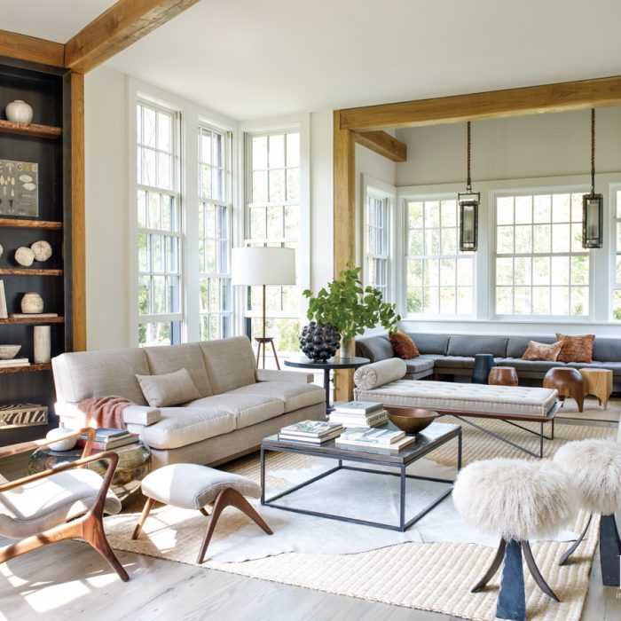 A custom sectional from Peruvian Touch fills the living room's bump out window. The pendants are from Martin Showroom in Napa Valley, California. The vintage steel and Mongolian lambswool stools are from Sputnik Modern.