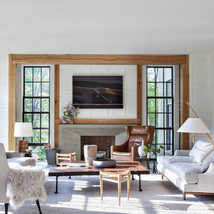 The family room is a cozy retreat complete with a vintage Borge Mogensen wing chair to curl up on next to the fireplace. Above one of the two sofas from Future Perfect, which are upholstered in Schumacher and Romo fabrics, hangs a photograph by Thomas Struth, which was placed by the couple's art advisor, Amy Snyder. The coffee table is from BDDW.