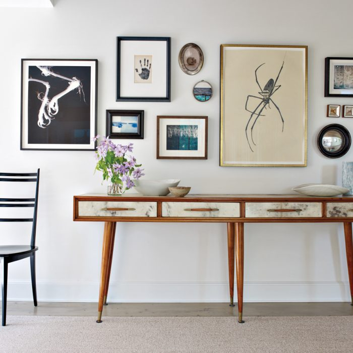 A 1950s Italian console from Flair anchors an art-filled space along a hallway. The vintage chair is from Dwayne Modern.