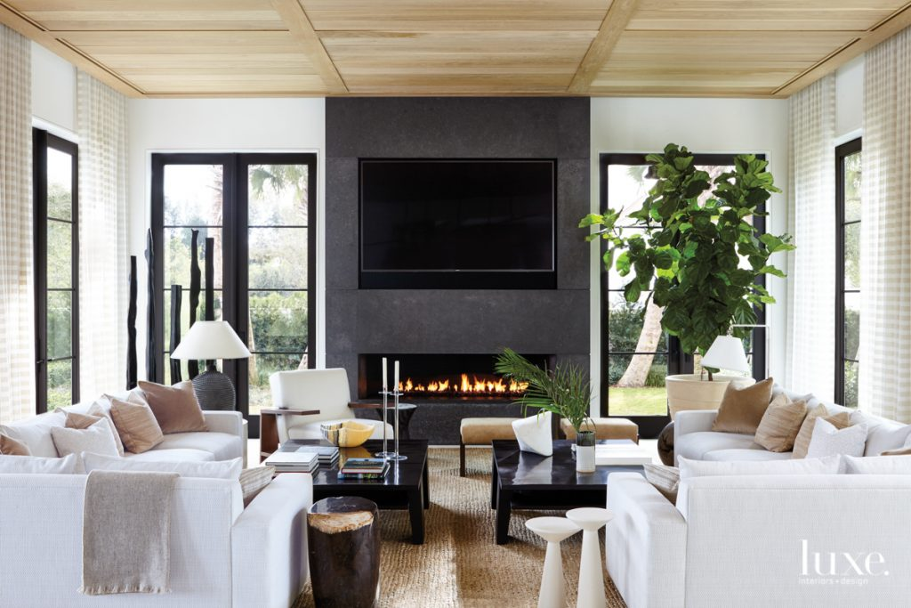 A dramatic limestone fireplace by...