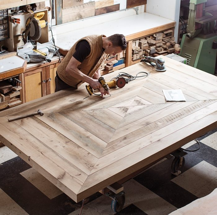 Custom furniture maker Gabriel Statsky works on a dining table that he's crafting from reclaimed white oak. The wood, originally the floor joists of an 1895 Kentucky barn, will be darkened by fuming and finished with a hard-wax oil by Rubio Monocoat.