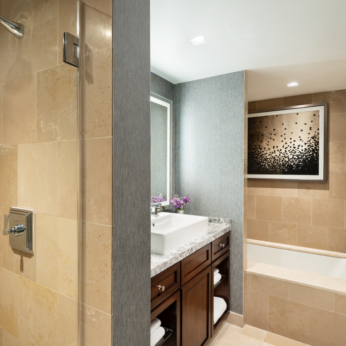 The Executive Suite touts exemplary bath amenities, including a soaking tub and marble-clad, walk-in shower.