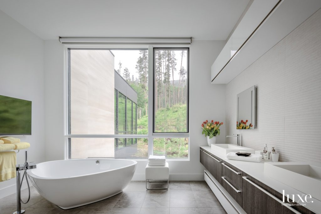 The serene master bathroom, which affords leafy treetop views, features a triangular soaking tub by Aquatica. The custom cabinetry is by Porcelanosa.