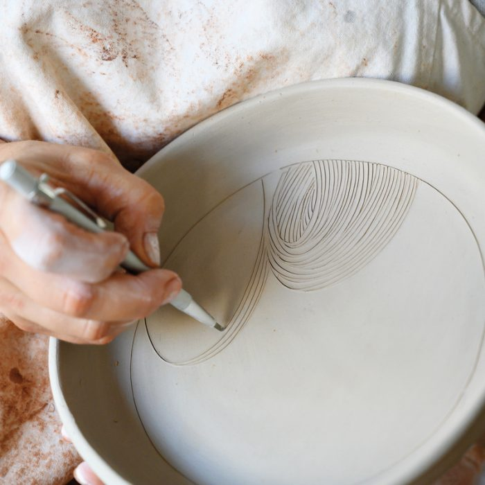 Artist Linda Fahey carves a woodblock-like pattern into a serving plate.