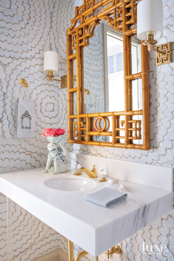 A powder bathroom is wallpapered...