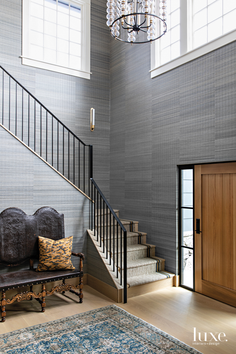 Double-height entry with grasscloth wallcovering.