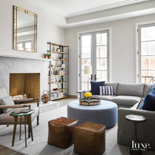 Who Says A Family-Friendly Home Can't Have Glam Accents? This Chicago Abode Gets It Right. gray living room with marble fireplace and blue ottoman