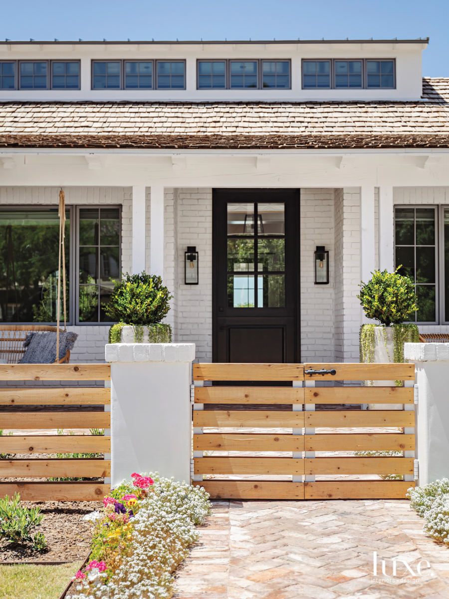 front door exterior with swinging chair and barn doors for a gate