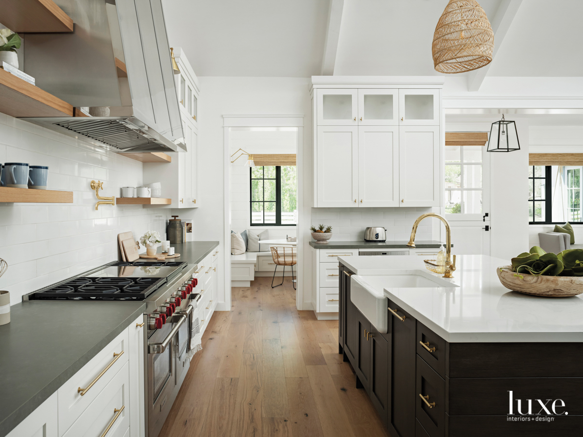 kitchen with a custom hood, island with white marble countertops and dark cabinetry