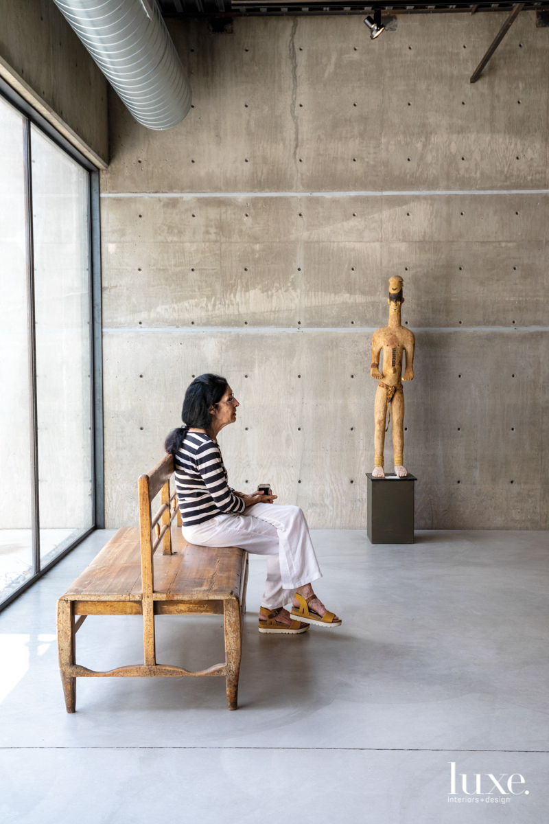 artist sitting on a bench looking at her studio with a sculpture in the background