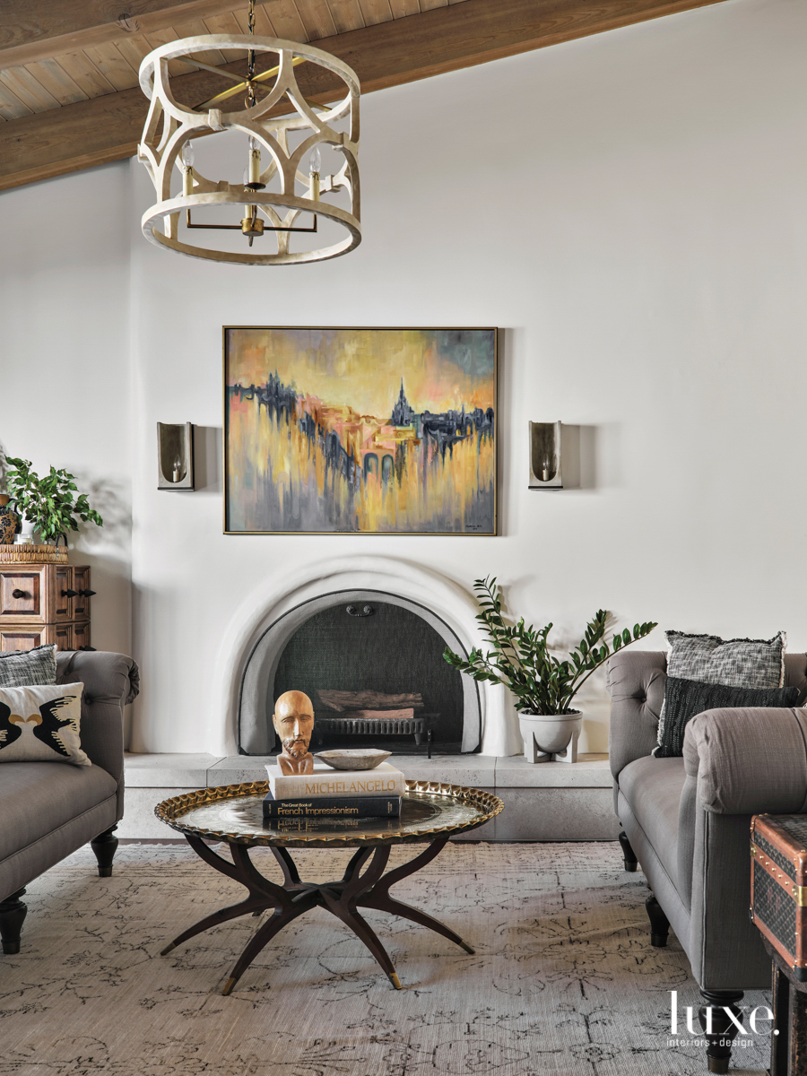 Vintage furniture and art sit in front of a fireplace in the living room