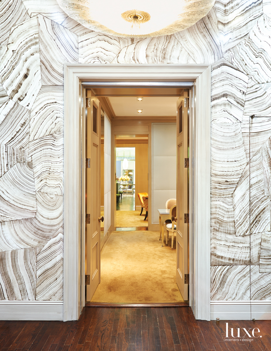doorway with wallcovering around the door and chandelier