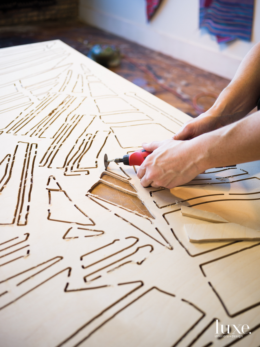 Dan Gunn hand cutting plywood in his studio.