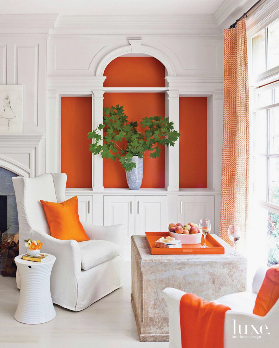 sitting area with white furniture and orange accents