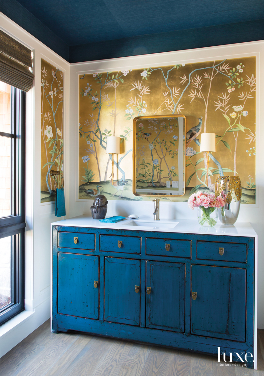bathroom with gold flower wallpaper and blue cabinetry