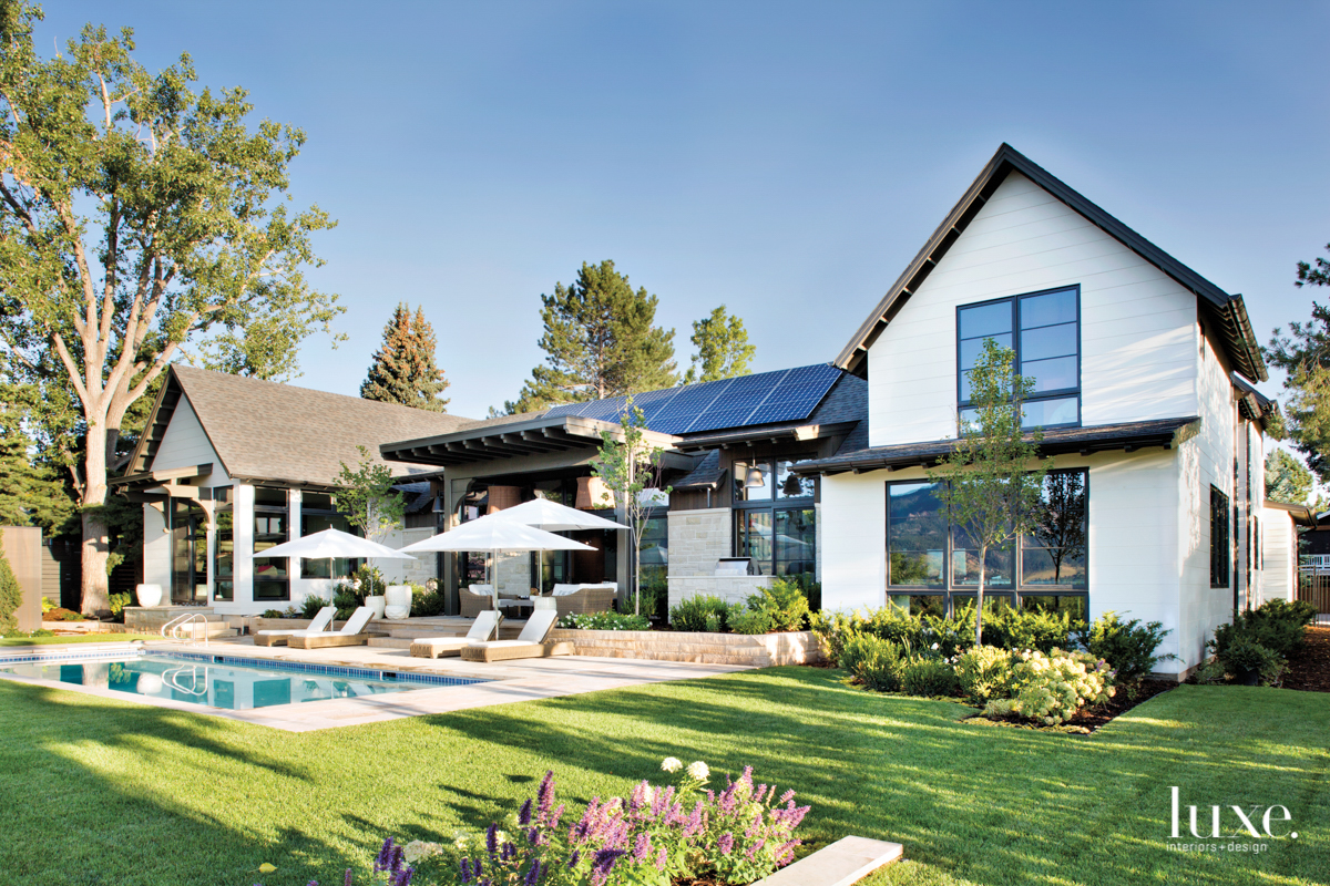 The exterior of a large white home with dark accents has large windows. There's also a large patio and pool.