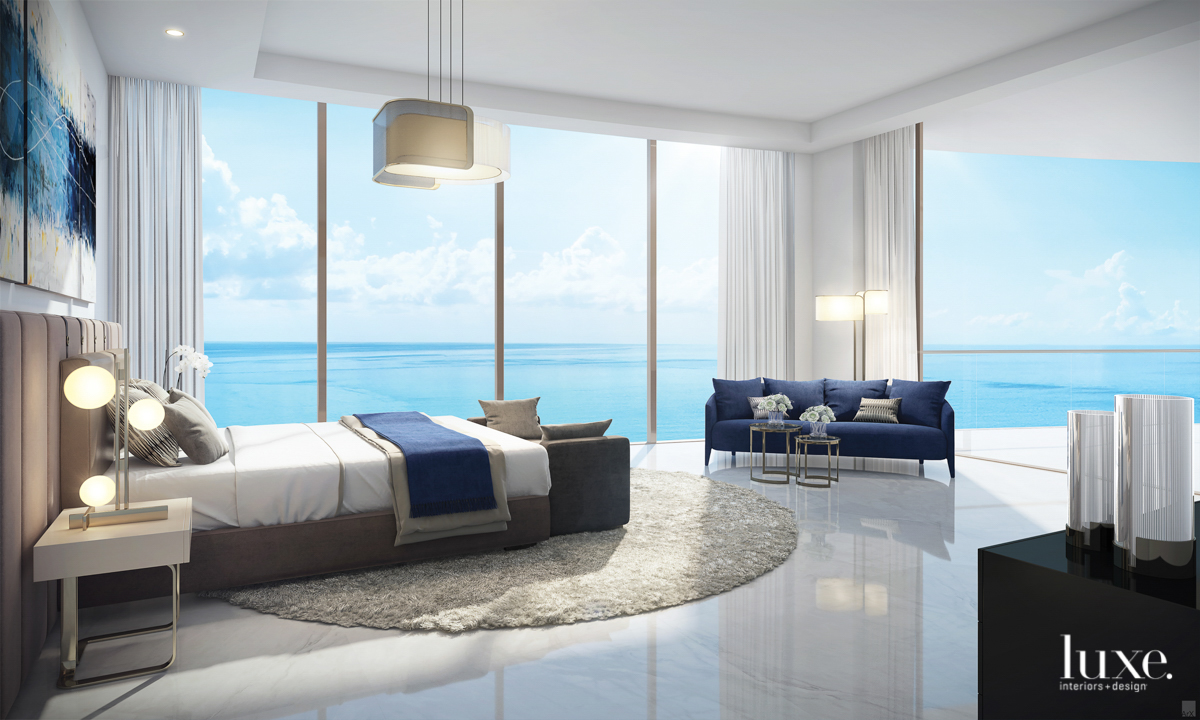 view of the ocean from bedroom with bed and couch