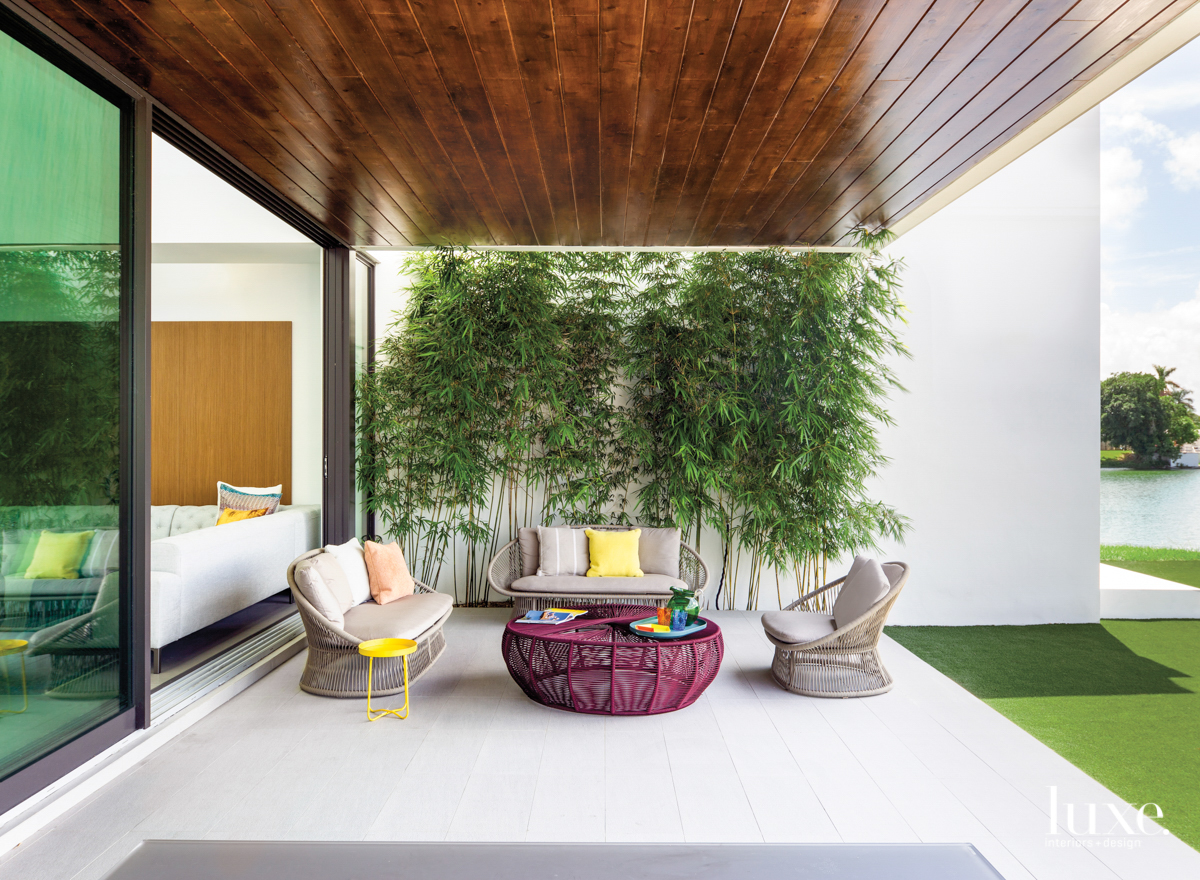 modern miami loggia with bamboo wall, gray furnishings and purple coffee table