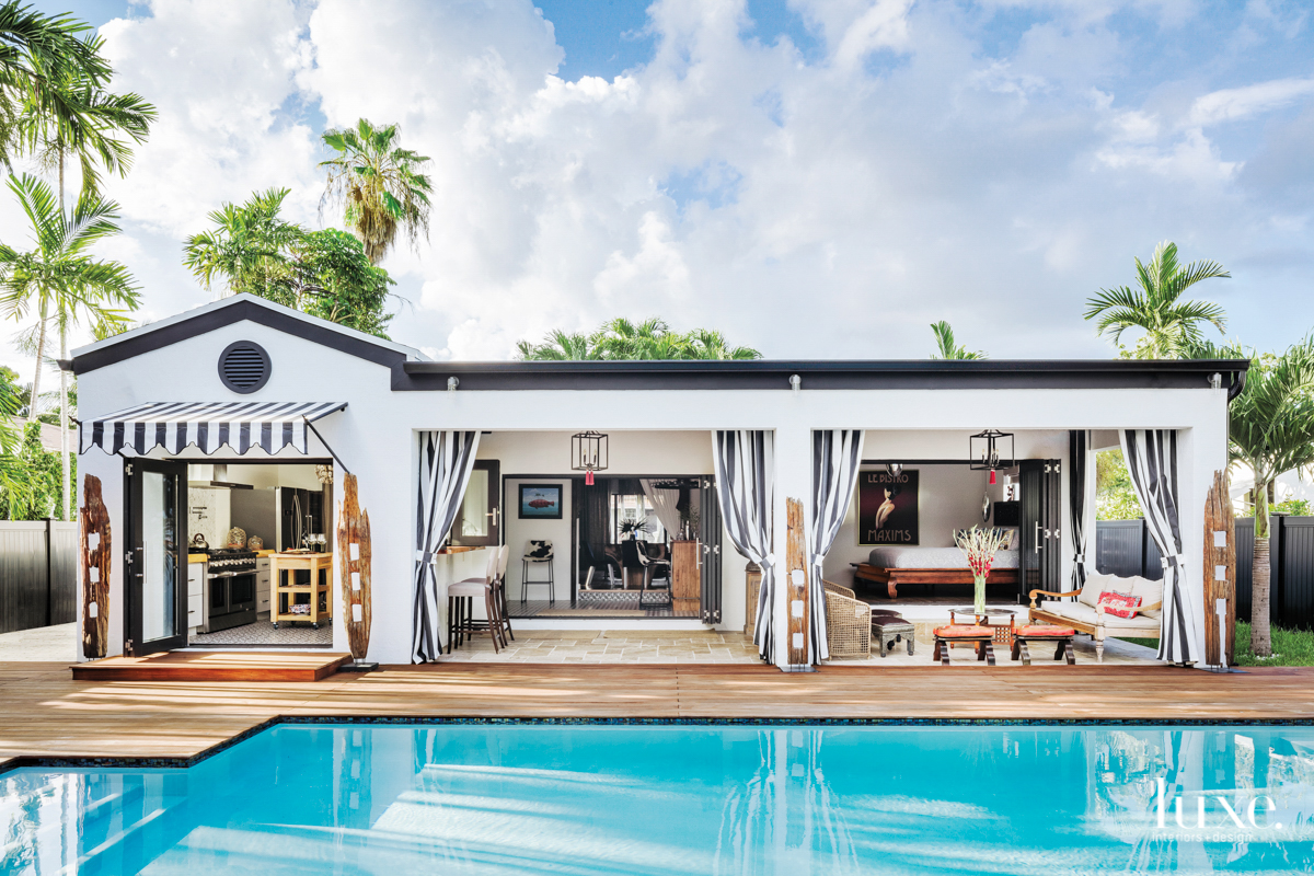 Back exterior of black and white midcentury Miami bungalow with pool