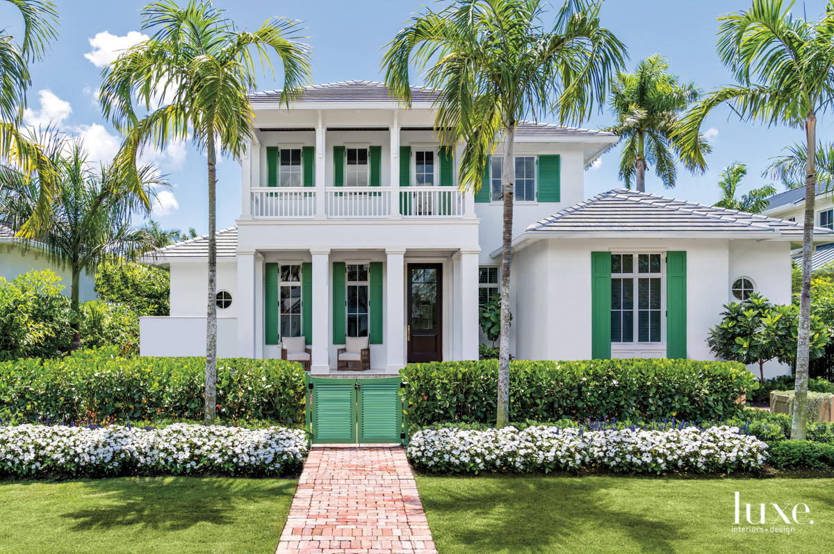 exterior of naples home from the front, white home with green shutters and balcony
