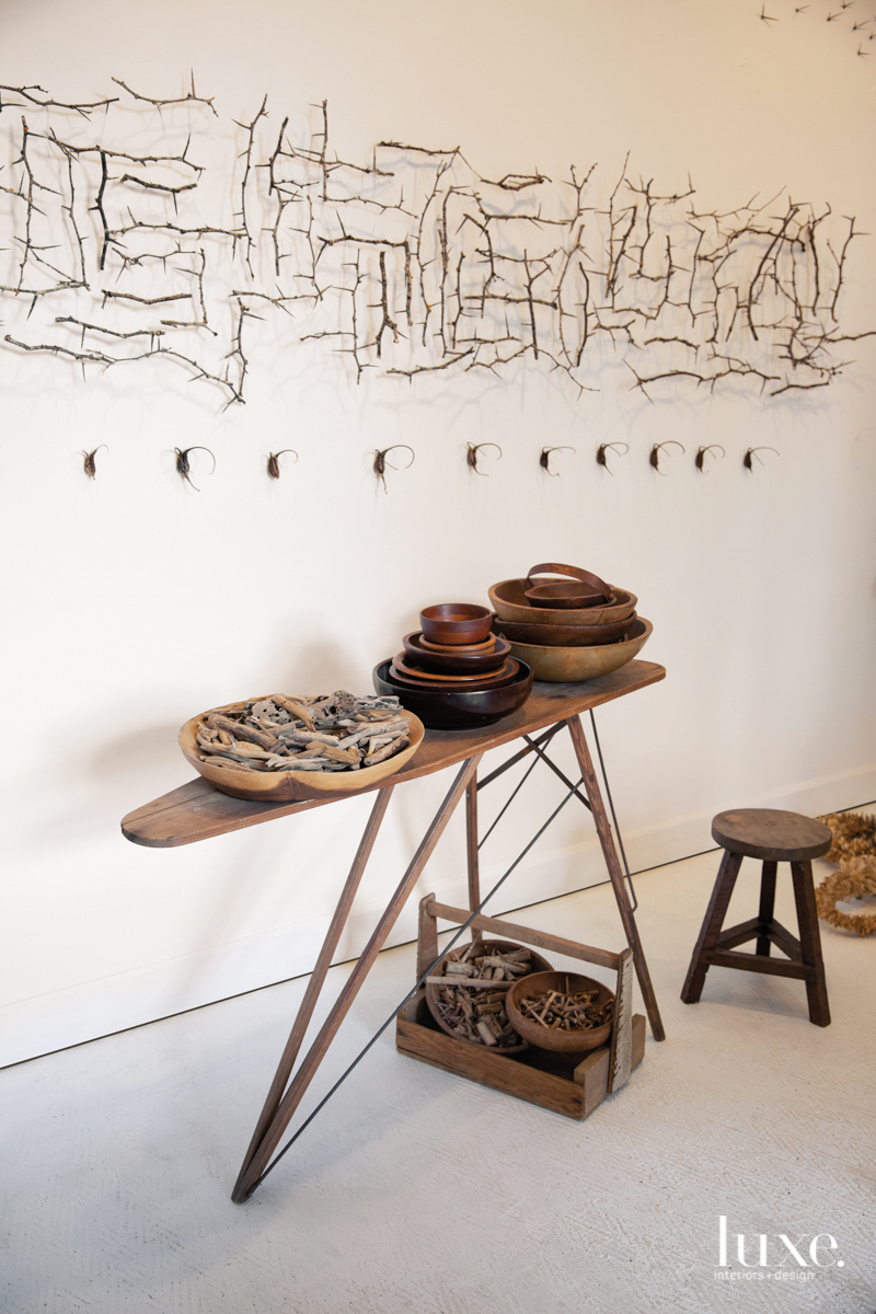 table with pots and branches of art on the wall