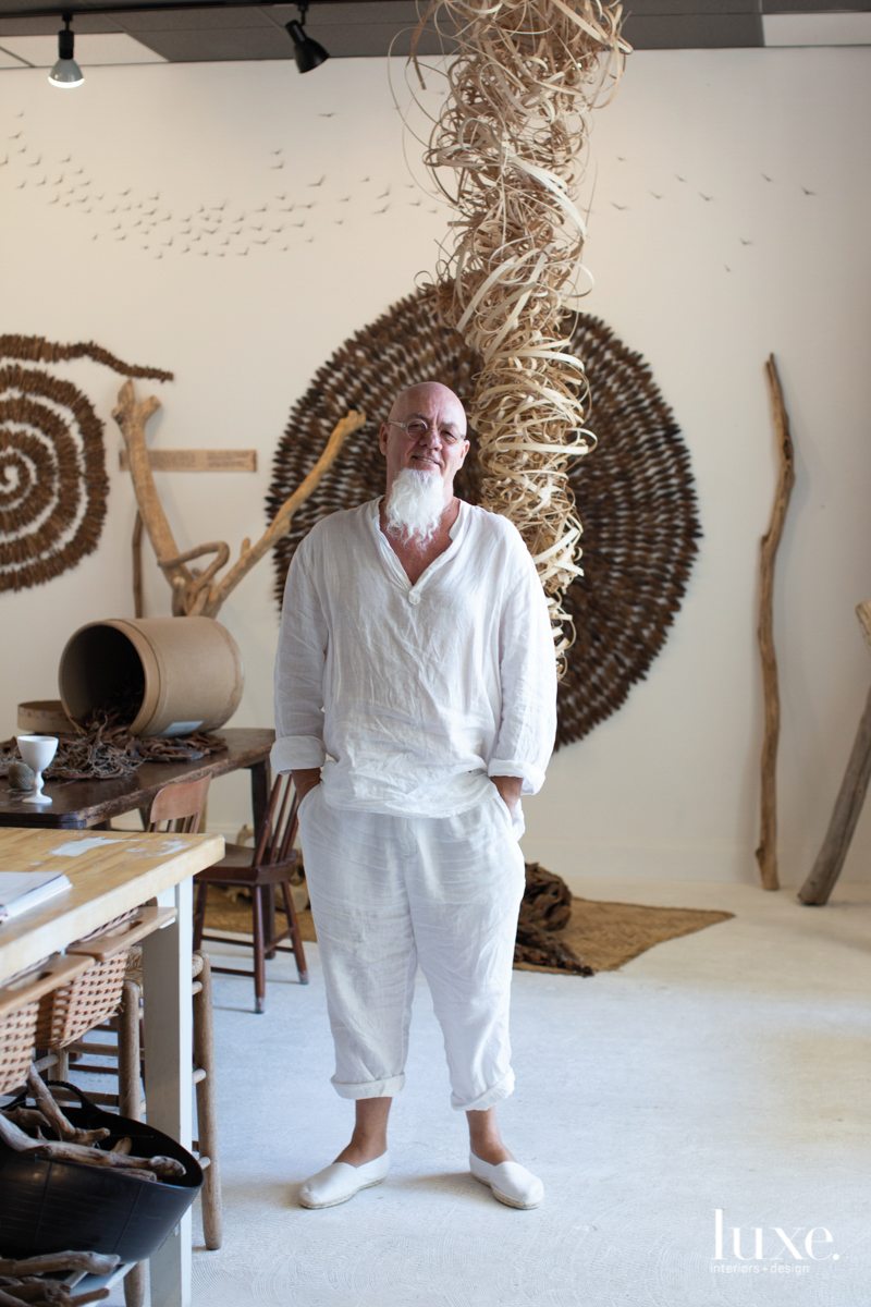 ran adler in his studio with pieces of wood art
