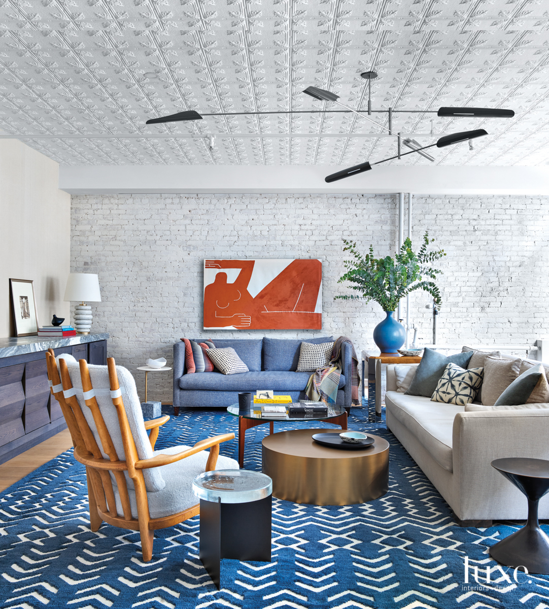 liivng room with textured ceiling, blue rug and orange art