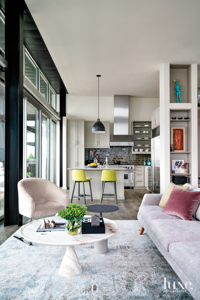 gray living area with adjoining kitchen with chartreuse bar stools