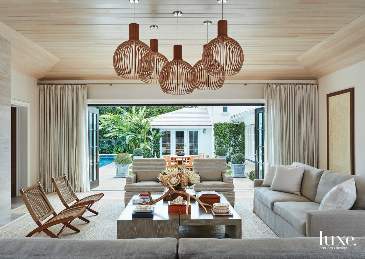 living room with open wall-to-wall dors and drapery with large wooden light fixtures