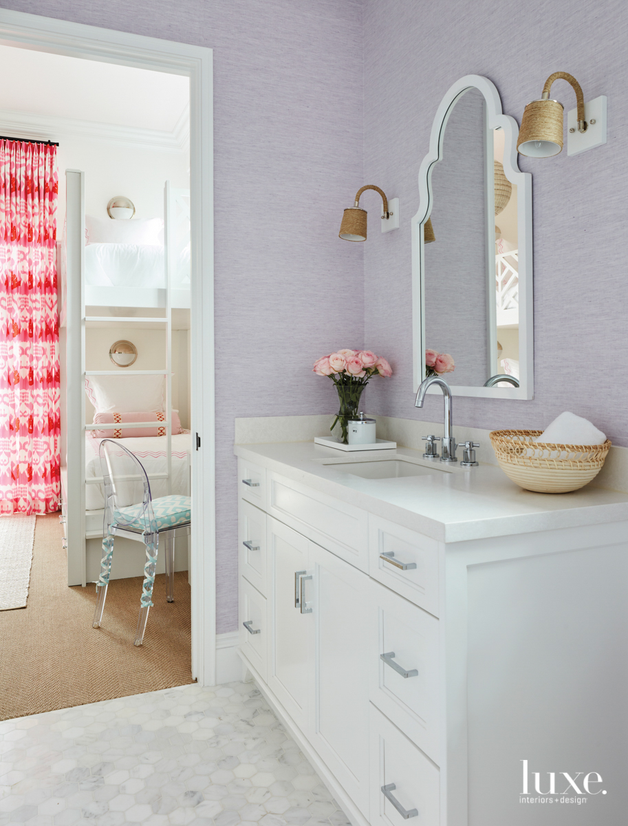 Bathroom with lavender wallcovering and...