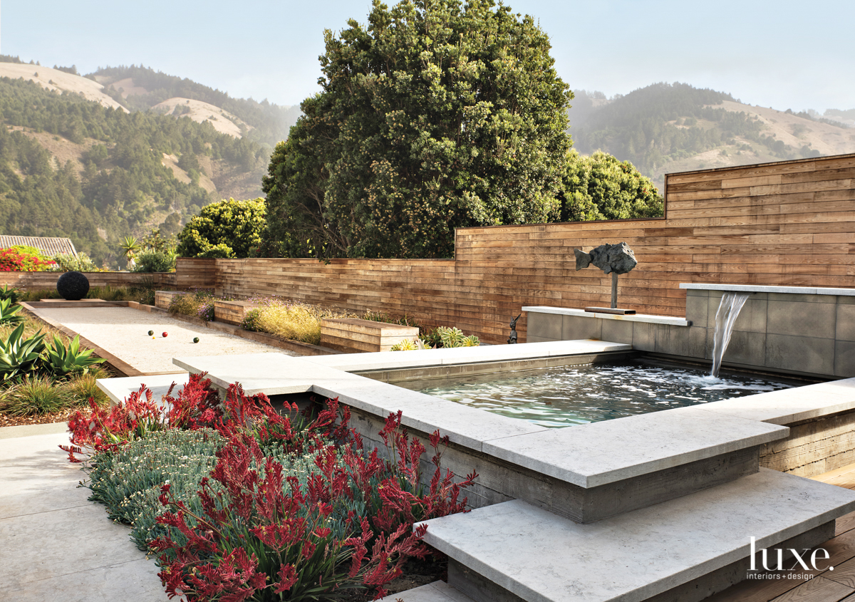 A backyard with a spa, sculpture and a bocce court. with mountain views.