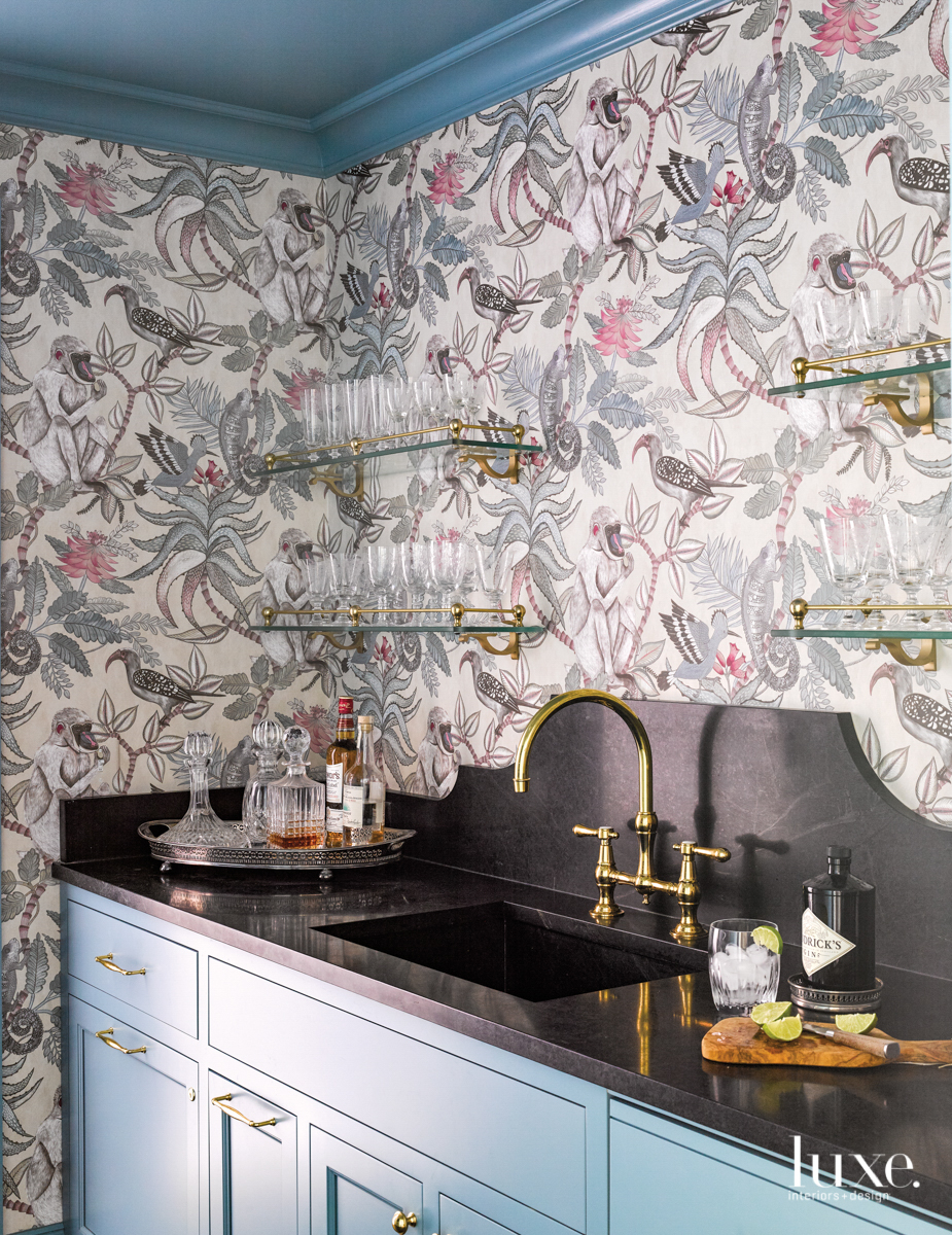 butler's pantry with plant and birds patterned wallpaper, blue cabinetry and black marble countertop