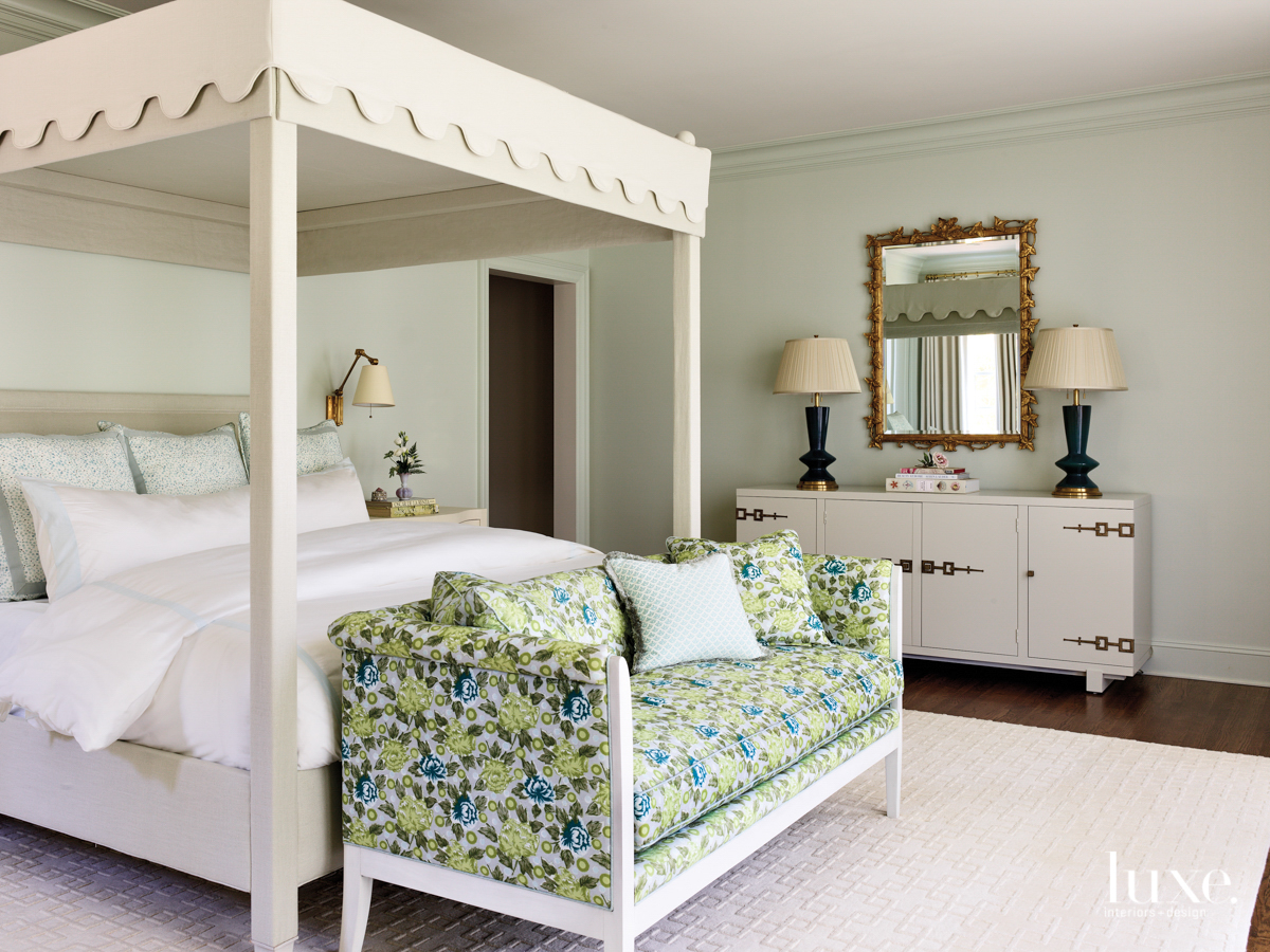 master bedroom with light green walls, a green flower patterned couch and canopy bed