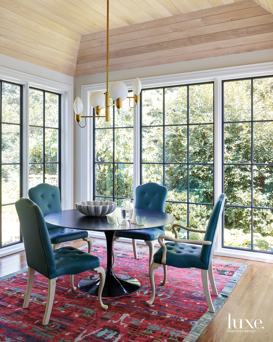breakfast room with floor-to-ceiling wandows, four blue chairs, a brass and white lg=ight fixture and red patterned rug