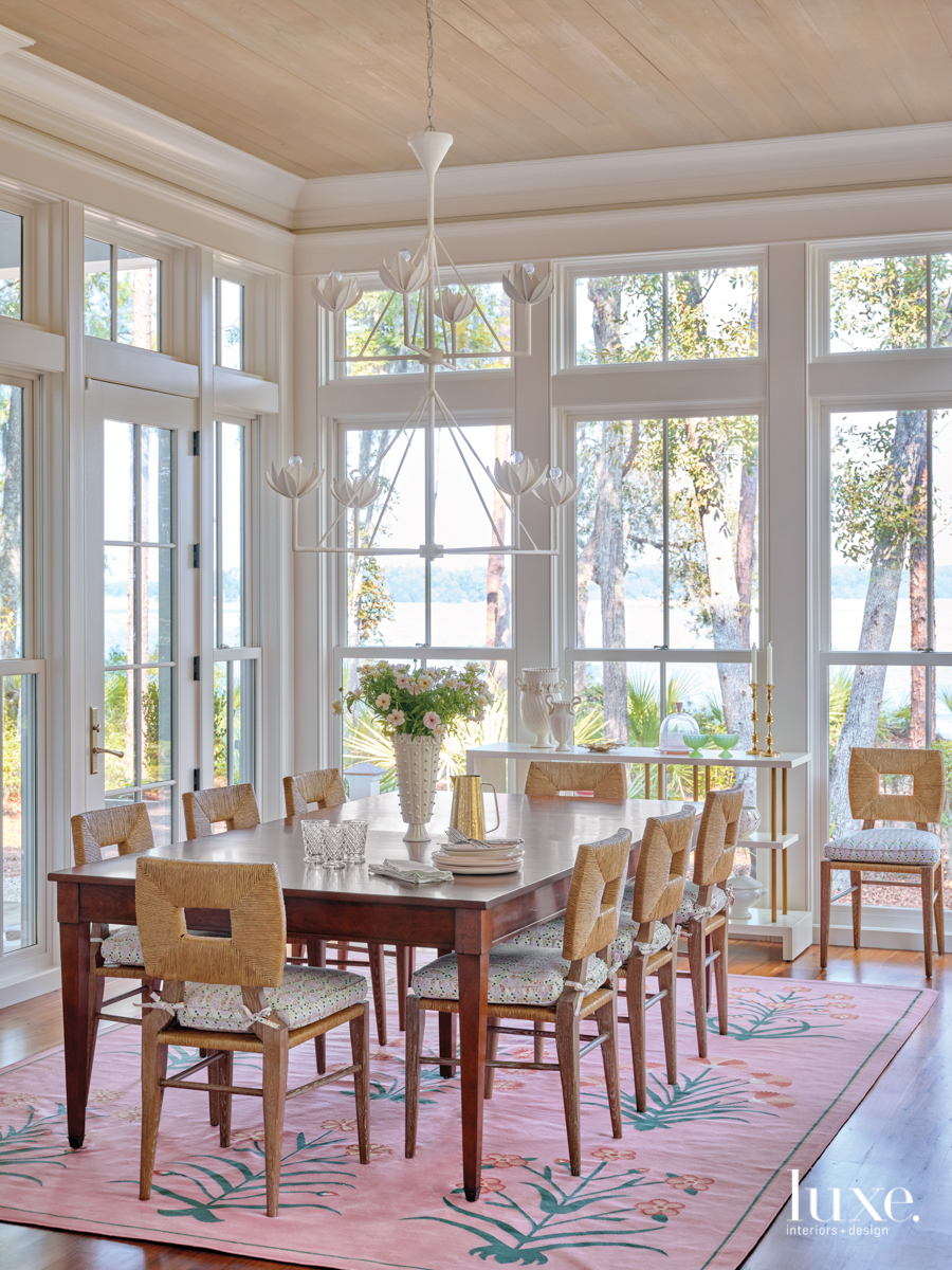 breakfast room with floor to cieling windows, pink rug and custom dining table