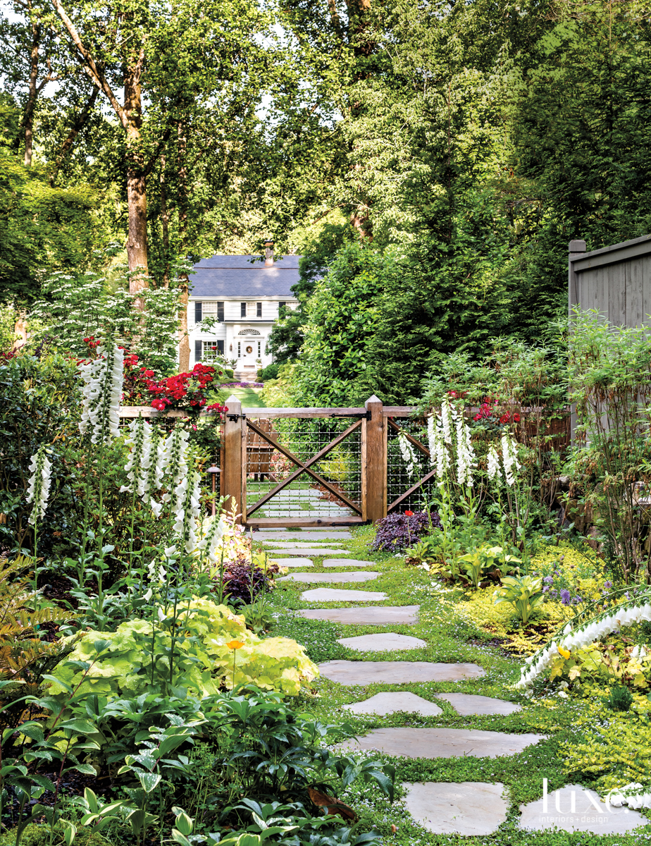 lush garden with stone walkway and wooden swinging gate