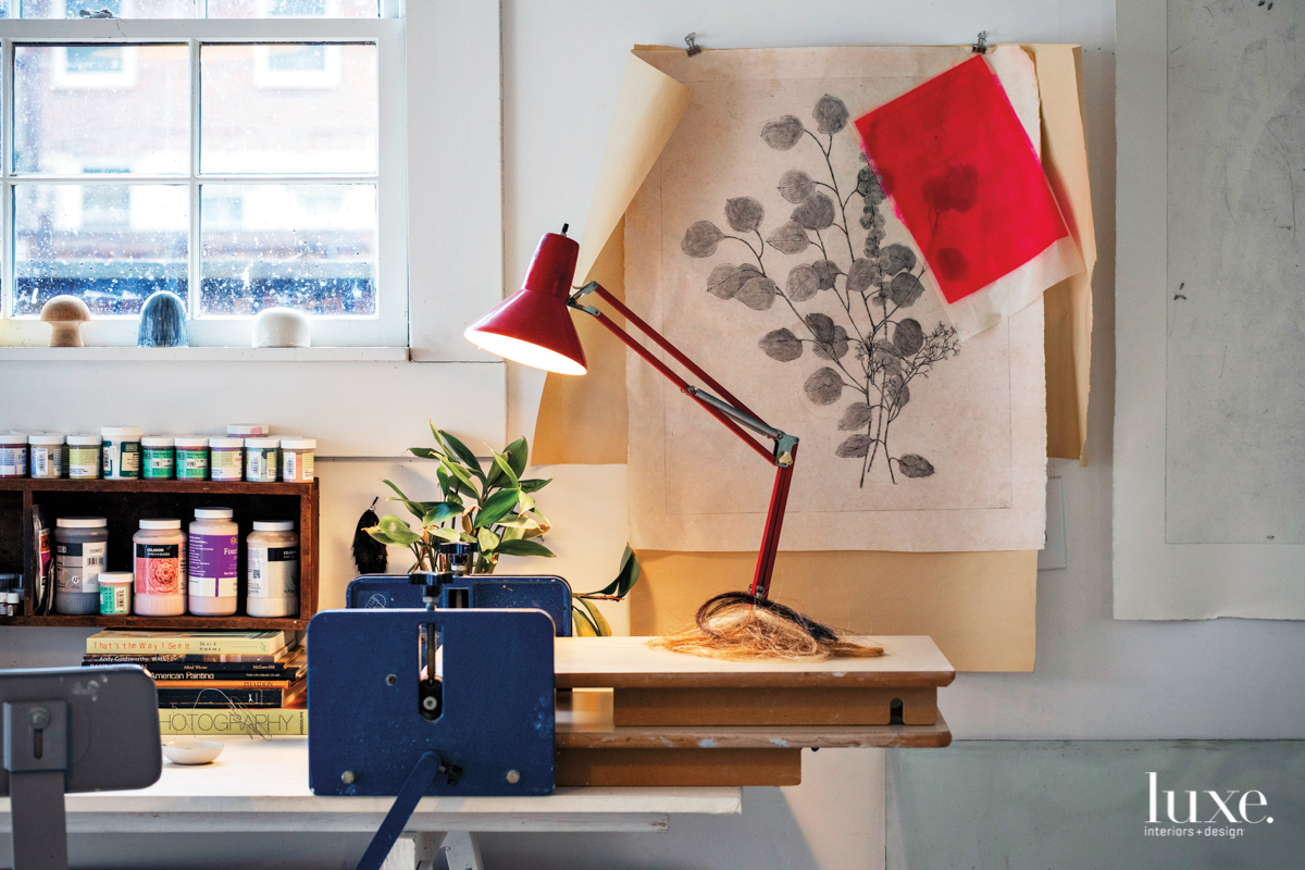 work desk with lamp, botanical artwork and lidded jars