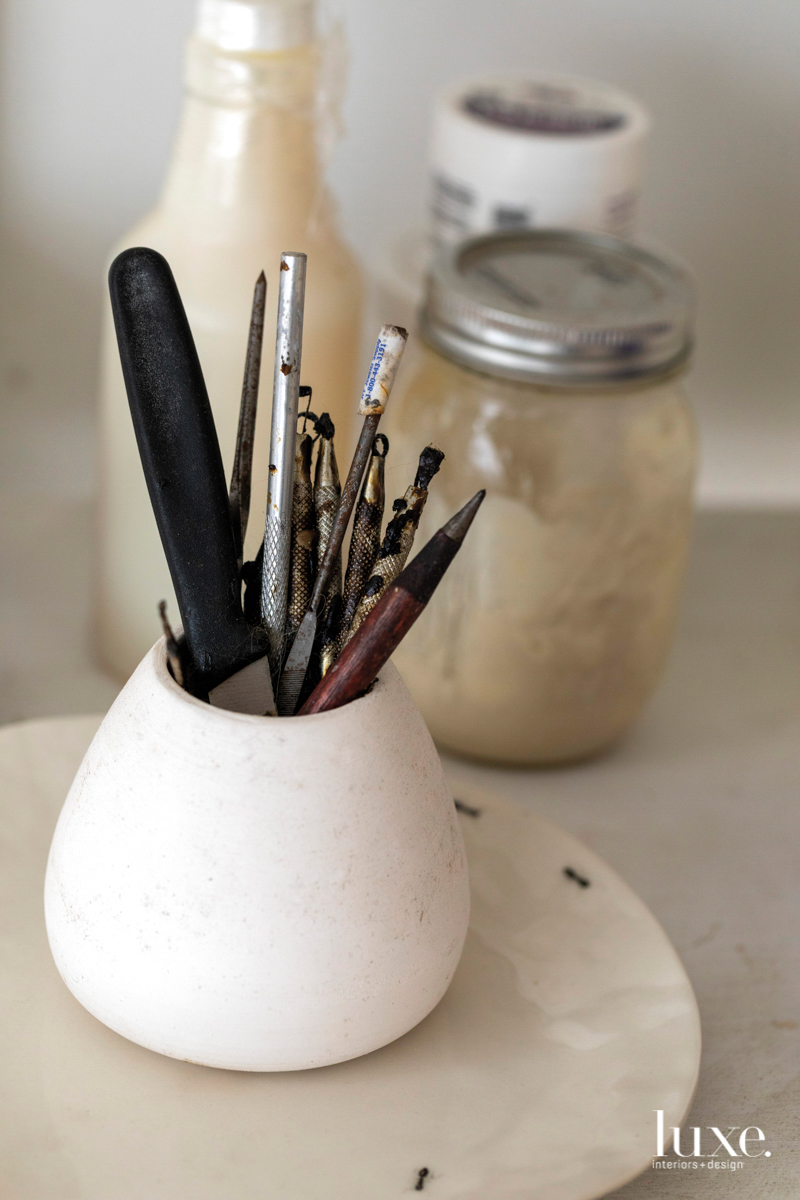 a ceramic pencil cup containing tools