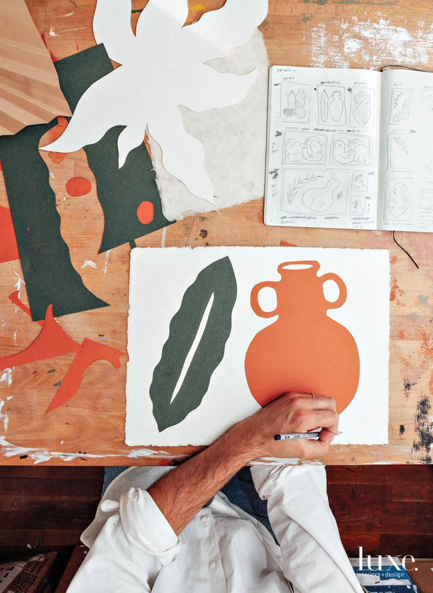 alvarez's hand working on another piece of art, orange painting of a pot