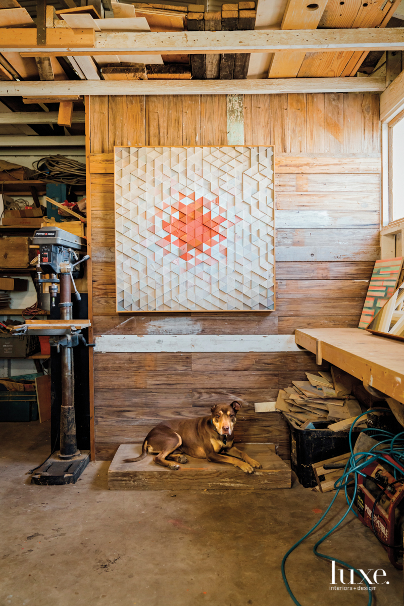 Aaron Michalovic's dog sitting below a wood collage in the artist's studio