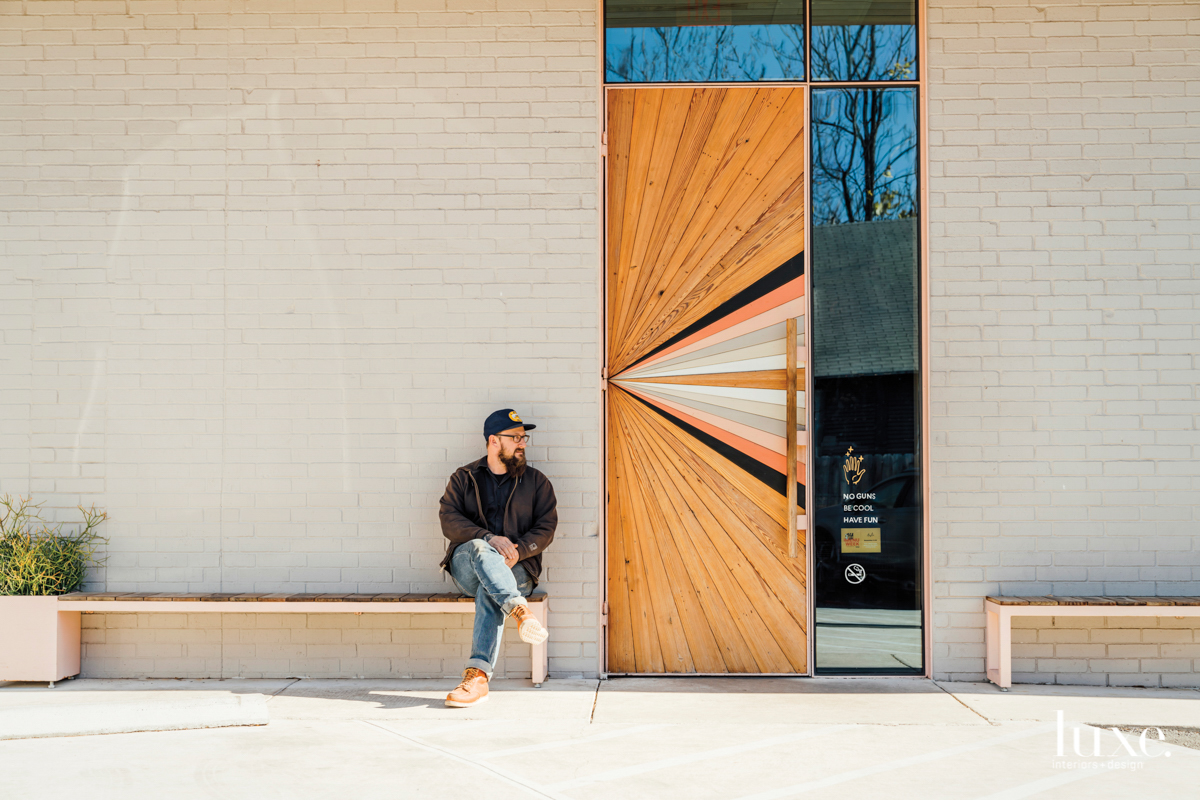 Aaron Michalovic sitting near a door he designed for Suerte